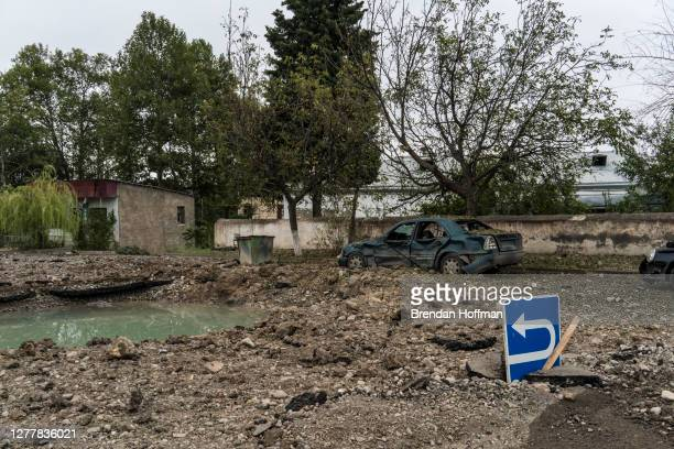 Destroyed cars and a crater in the road that are the result of a reported drone strike the previous day, on October 1, 2020 in Martakert,...