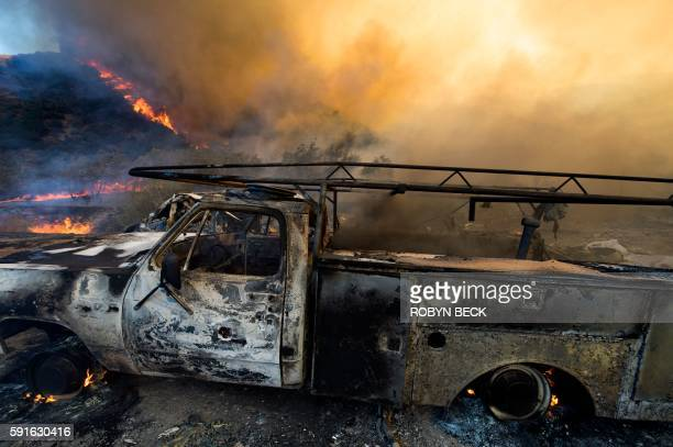 Destroyed cars smolder after the Blue Cut Fire burnt a small community near Wrightwood California August 17 2016 / AFP / Robyn BECK