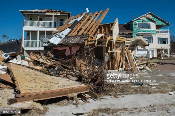 A destroyed home that was washed across the street rests in front of two other damaged buildings in Port Saint Joe Florida on October 12 two days...