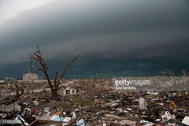 Destroyed homes and debris cover the ground as a second storm moves in on May 23, 2011 in Joplin, Missouri. A powerful tornado ripped through the...