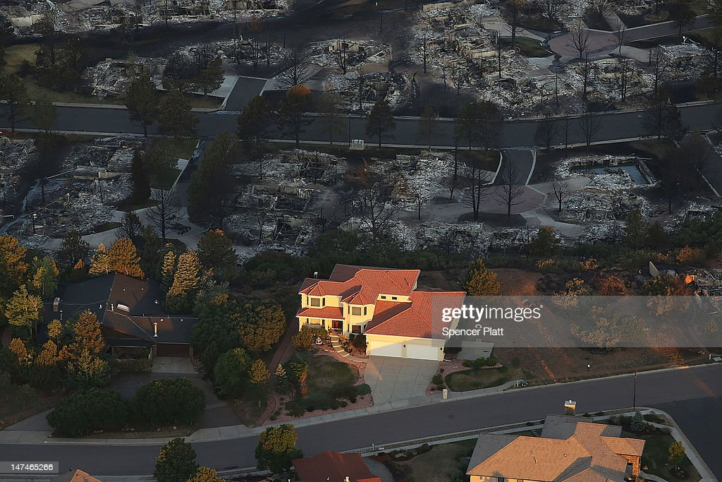 Destroyed homes sit beside a home left untouched by fire in a neighborhood affected by the Waldo Canyon fire on June 30, 2012 in Colorado Springs, Colorado. The massive fire, which has eased with the help of cooler temperatures and lighter winds, has destroyed hundreds of homes and forced more than 35,000 people to flee. The fire was estimated at 17,073 acres and was 25 precent contained with some evacuees being let back into their neighborhoods. A second body has been located in a burned home while others are still reported missing.