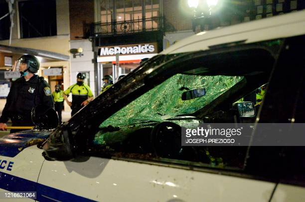 A destroyed police cruiser is guarded by officers during clashes with protesters after a demonstration over the death of George Floyd an unarmed...