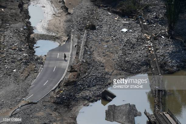 Destroyed railway track is seen as a man walks along the destroyed B267 federal highway between Rech and Mayschoss, near the municipality of...