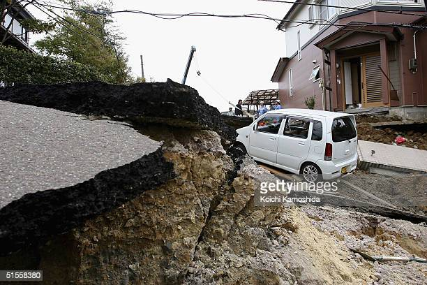 Destroyed road and cars are seen on the verge of sliding away, on October 25, 2004 in Nagaoka, Japan. A series of powerful earthquakes rocked...