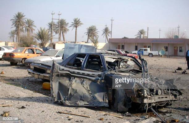 A destroyed vehicle is seen following a suicide car bomb that killed seven policemen and wounded 15 others at a police station in Baiji north of...