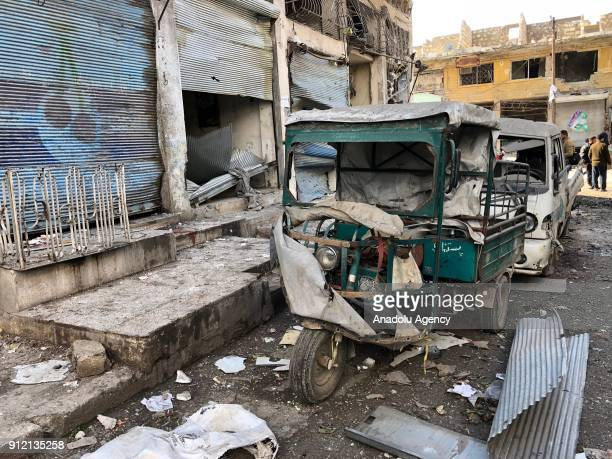 Destroyed vehicles and damaged buildings are seen after an airstrike at a marketplace in the deescalation zone of Eriha district of Idlib Syria on...