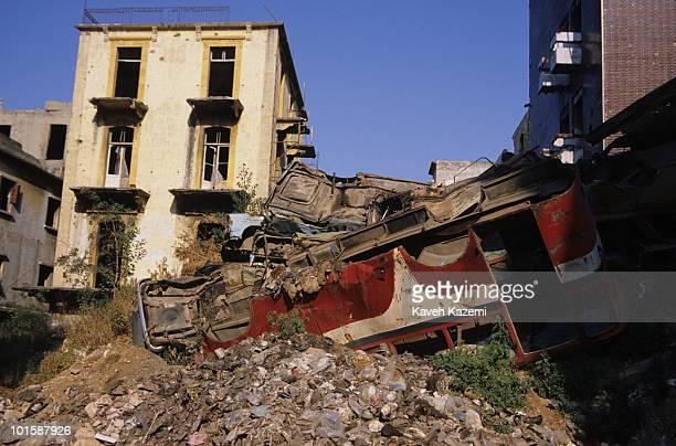 Destroyed vehicles are piled up on top of rubble near the green line in Beirut Lebanon during the civil war 12th June 1986