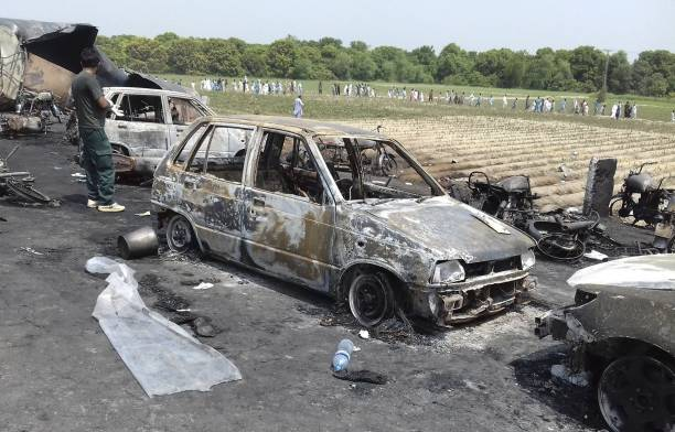 Destroyed vehicles are seen at the site of an overturned oil tanker which caught fire and killed 123 people after the explosion near the Pakistani...