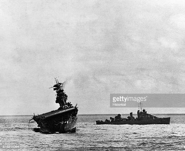 A destroyer comes to the aid of the listing aircraft carrier USS Yorktown which was hit by Japanese bombs and torpedoes during the Battle of Midway...