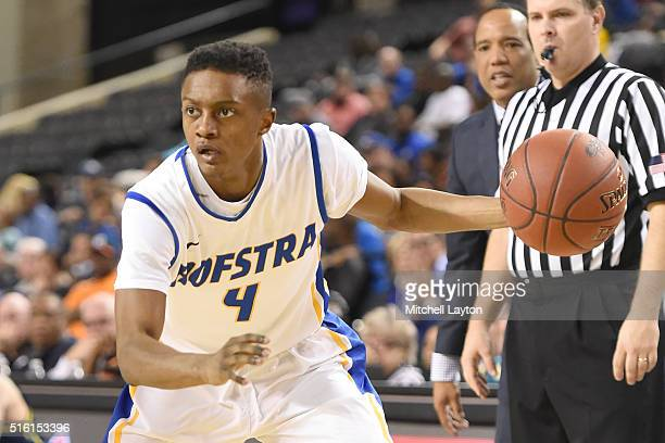 Desure Buie of the Hofstra Pride dribbles the ball during the Colonial Athletic Conference Championship college basketball game against the North...