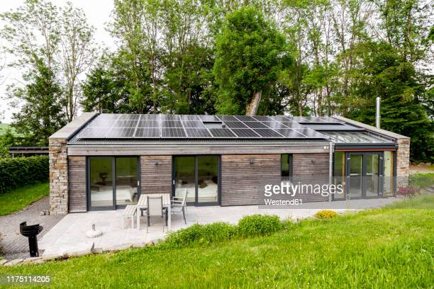 detached house with solar panels on the roof - haus stock-fotos und bilder