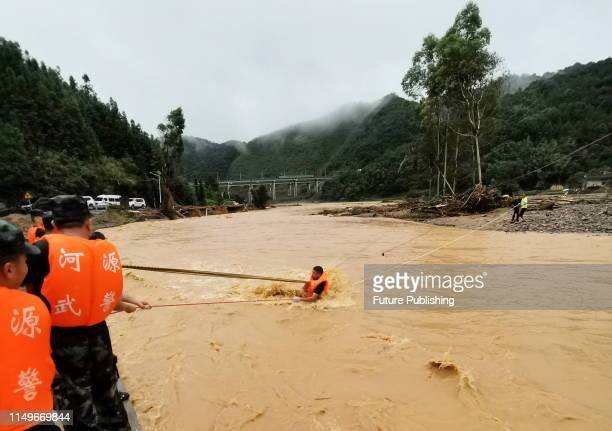 A detachment of armed police officers uses ropes to cross a flooded river and move people along a mountain road in Heyuan south China's Guangdong...