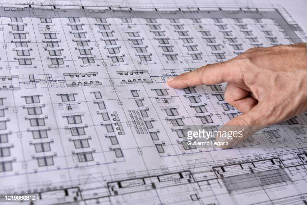 Detail as an architect points at the plans of a temporary hospital under construction at Corferias convention center on April 15 2020 in Bogota...