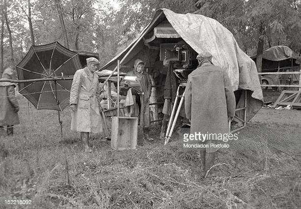 A detail behind the scenes during filming of King Vidor's 'War and Peace' some technicians prepare a big tent in order to cover the film camera...