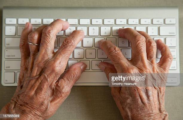 detail - elderly woman typing on wireless keyboard - timothy hearsum stock pictures, royalty-free photos & images