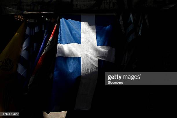 A detail from a Greek national flag is seen as it hangs outside a street kiosk in Athens Greece on Friday Aug 9 2013 Greece's economy contracted for...