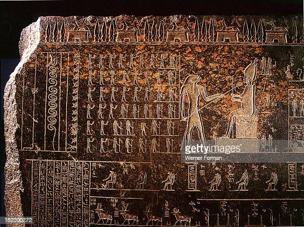 Detail from a sarcophagus depicting Horus reviving with the ankh sign of life his father Osiris while standing deities raise their hands in adoration...