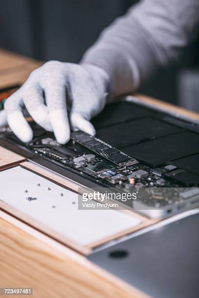 Detail image of male technician repairing digital tablet at electronics store