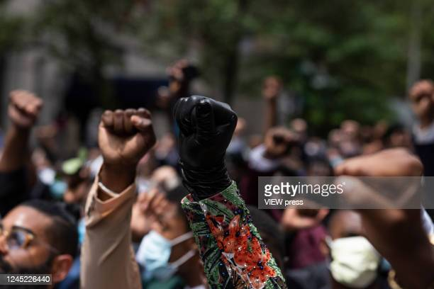 Detail in Protesters fist in march against the death of George Floyd and hold the funeral on June 4, 2020 in Harlem, New York. The white police...