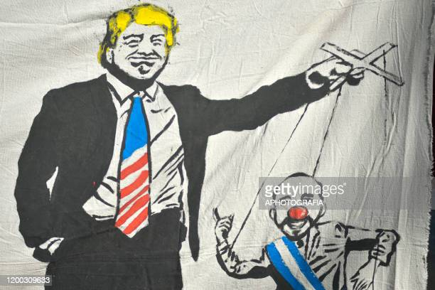 Detail of a banner depicting President of the United States Donald Trump and President of El Salvador Nayib Bukele during a protest against...