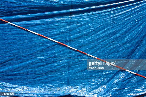 detail of a blue tarpaulin and striped cordon tape - 防水シート ストックフォトと画像