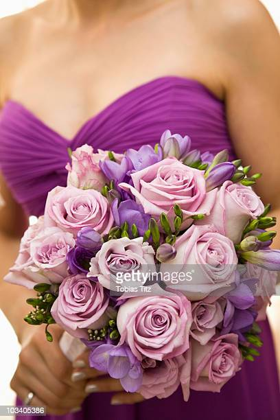Detail of a bridesmaid holding a bouquet of flowers