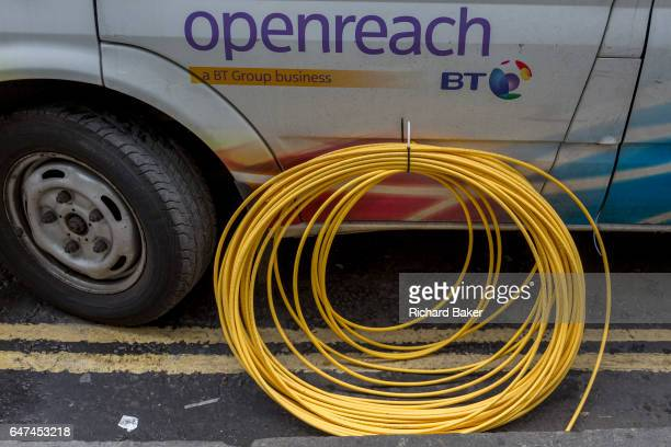Detail of a BT Openreach van and a coil of yellow broadband fibre cable on the ground and awaiting installation on 16th February 2017 in the City of...