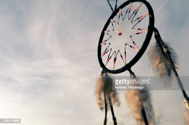 Detail of a dreamcatcher against bright evening sky.