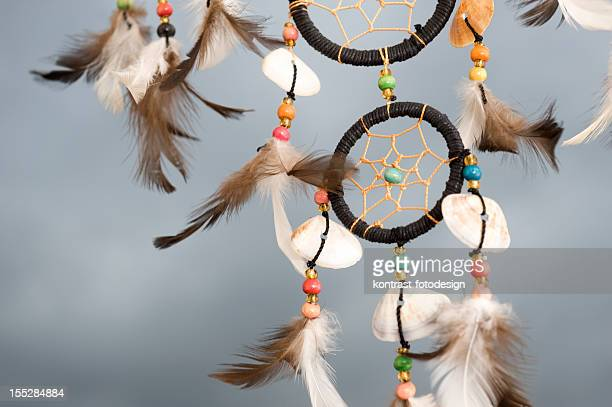 Detail of a dreamcatcher against dramatic grey  sky.