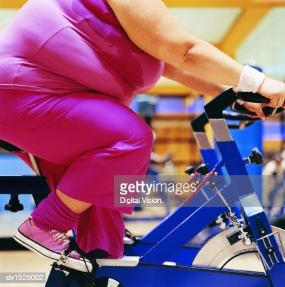 detail of a fat woman riding an exercise bike in a gym
