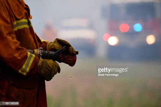Detail of a fire hose held by a CFA crew member is pictured on November 21 2019 in St Albans Australia Most of NSW remains under severe or very high...