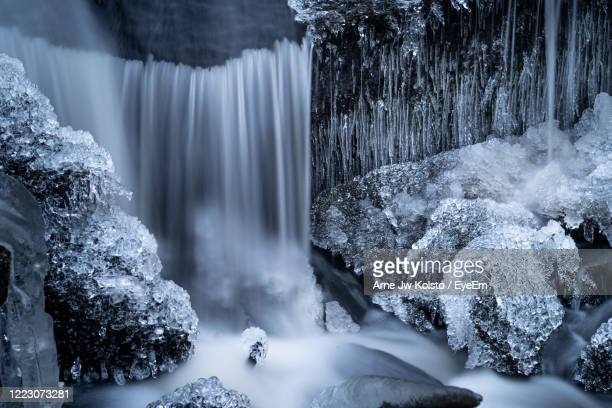 detail of a frozen small waterfall in a forest creek with icicles - arne jw kolstø stock pictures, royalty-free photos & images