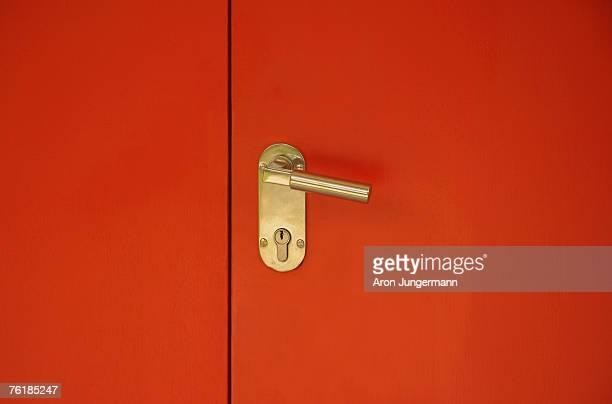 Detail of a gold door handle on a red door