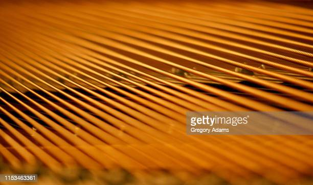 detail of a grand piano showing the geometric pattern of the strings - musical instrument string stock pictures, royalty-free photos & images