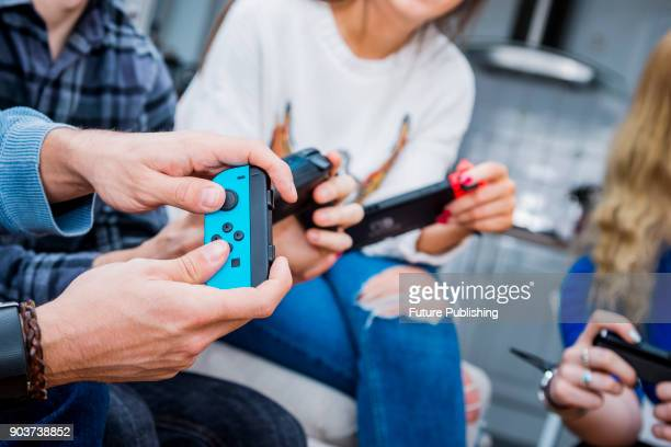 Detail of a group of men and women playing video games with a Nintendo Switch console and Joy Con wireless controllers, taken on March 7, 2017.