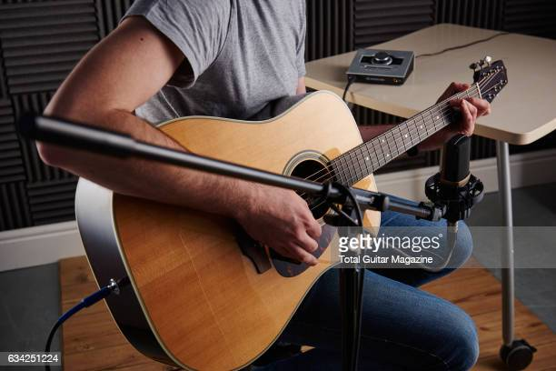 Detail of a guitarist recording a song with an AKG C314 multi-pattern condenser microphone and Universal Audio Apollo Twin interface, taken on April...