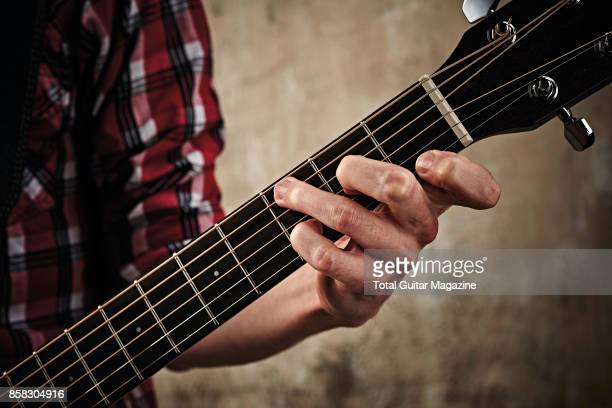 Detail of a guitarist's hand playing a slash chord on a Fender CD60S AllMahogany acoustic guitar taken on March 16 2017