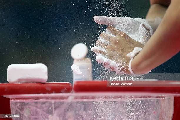 Detail of a gymnastics putting chalk on her hands in the Artistic Gymnastics Women's Team qualification on Day 2 of the London 2012 Olympic Games at...