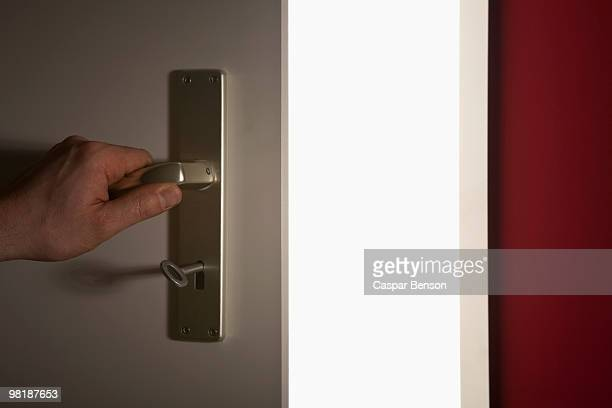 detail of a hand opening a door onto a bright room - magic doors stock pictures, royalty-free photos & images