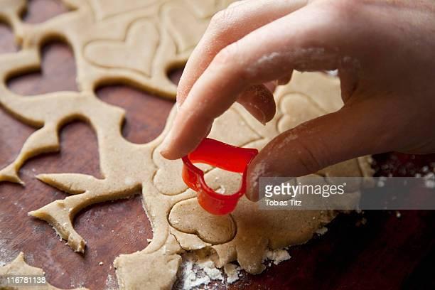 Detail of a hand using a heart shape cookie cutter