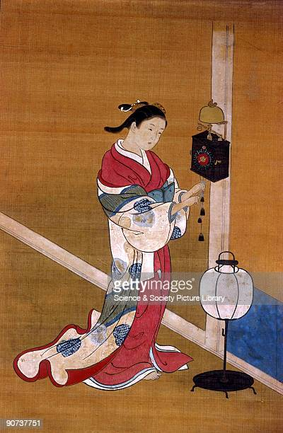 Detail of a Japanese painting on silk by Nishikawa Sukenobu of the Edo period showing a woman in a kimono winding up a weightdriven wall clock With a...