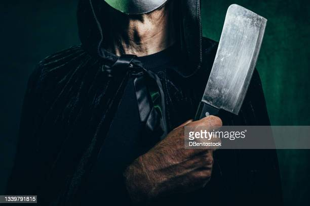 detail of a knife gripped by a menacingly toned man wearing a hooded cape and halloween killer mask, in a dark room with a victorian velvet background and green lighting. - 13日の金曜日 ジェイソン ストックフォトと画像