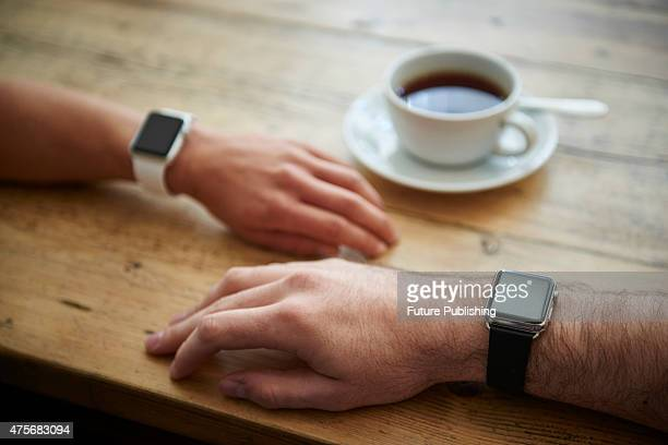 Detail of a man and woman wearing Apple Watches while sitting inside a cafe taken on May 21 2015