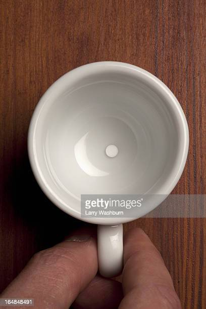 detail of a man holding a ceramic cup containing a tablet - dosis stock-fotos und bilder