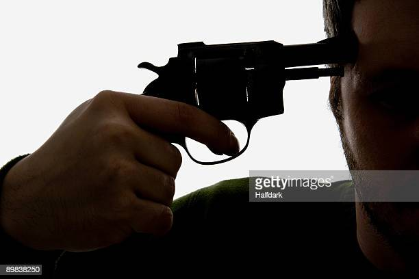 detail of a man holding a gun to his head - suicidio fotografías e imágenes de stock