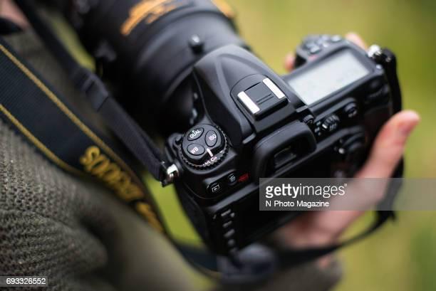 Detail of a man holding a Nikon D300s digital SLR camera taken on July 15 2016