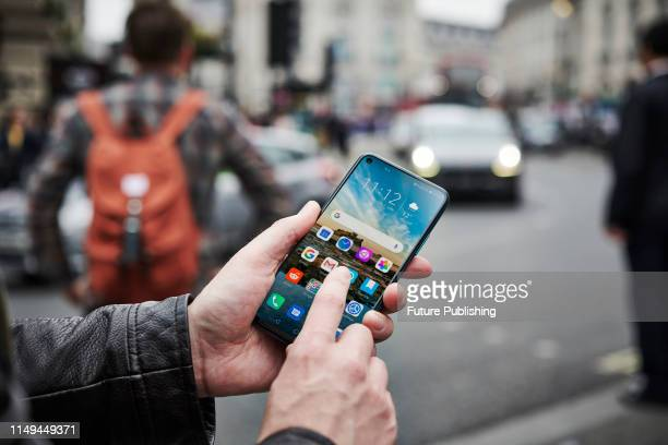 Detail of a man holding up an Honor 20 Pro smartphone while waiting to cross the street, on June 4, 2019.