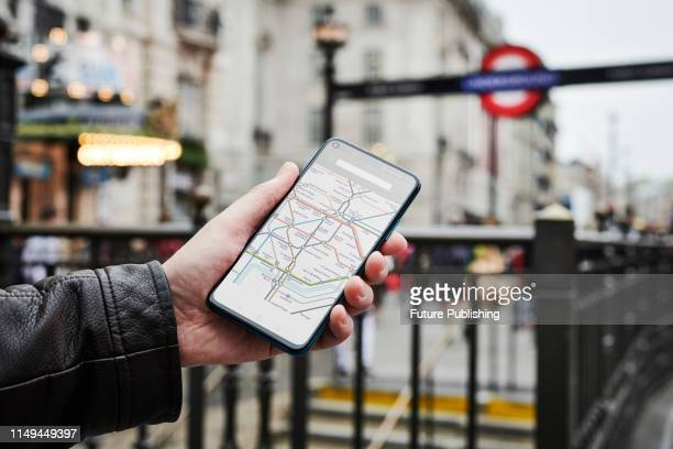 Detail of a man outside a London Underground tube station while holding an Honor 20 Pro smartphone with a rail map visible on screen on June 4 2019