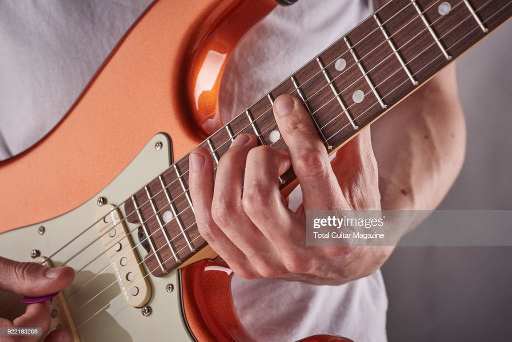 Detail of a man photographed playing an electric guitar for a feature on rhythm and timing techniques, taken on July 4, 2017.