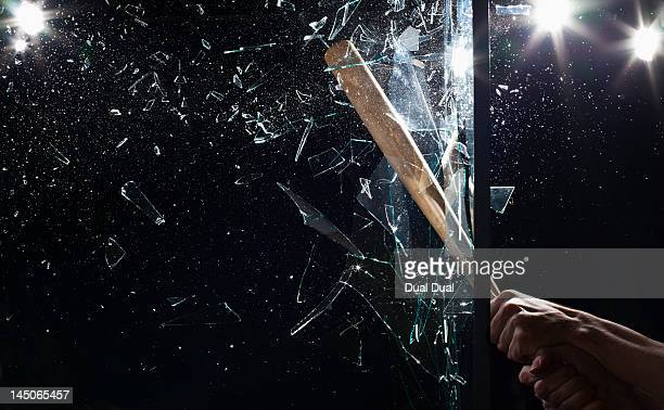 detail of a man smashing glass with a baseball bat - bate de béisbol fotografías e imágenes de stock